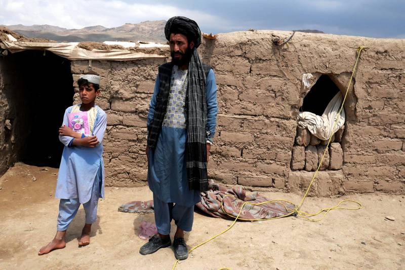 Pictured: Khan Mohammad, 40, with one of his sons, standing outside of the mud hut they now call home, having fled their village due to drought. The family now lives in an unofficial IDP camp in Herat. Photo by Charlie Faulkner May 2021