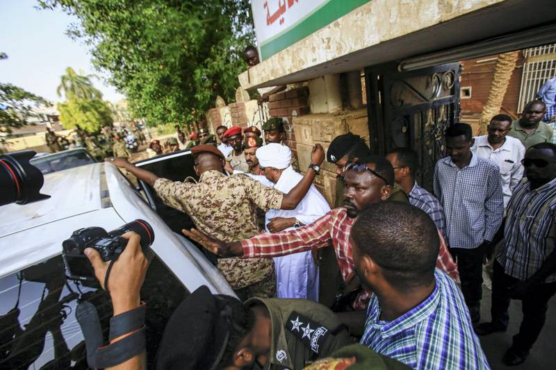 Sudan's ousted president Omar al-Bashir is escorted into a vehicle as he returns to prison following his appearance before prosecutors over charges of corruption and illegal possession of foreign currency, in the capital Khartoum on June 16, 2019. - Bashir was On June 16 seen in public for the first time since being ousted, as he was driven to the prosecutor's office. The former strongman, who ruled his northeast African nation with an iron fist for three decades, was toppled on April 11 after weeks of protests against his reign. (Photo by ASHRAF SHAZLY / AFP)