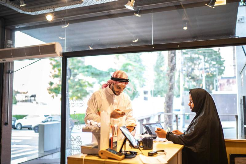Arab Middle East man doing mobile payment at convenience store