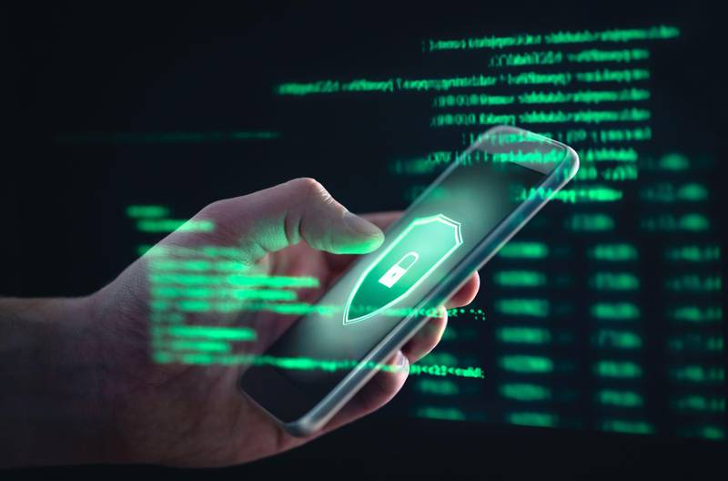 2B8D0TY Phishing, cyber security, online information breach or identity theft crime concept. Hacked phone. Hacker and cellphone with hologram data.