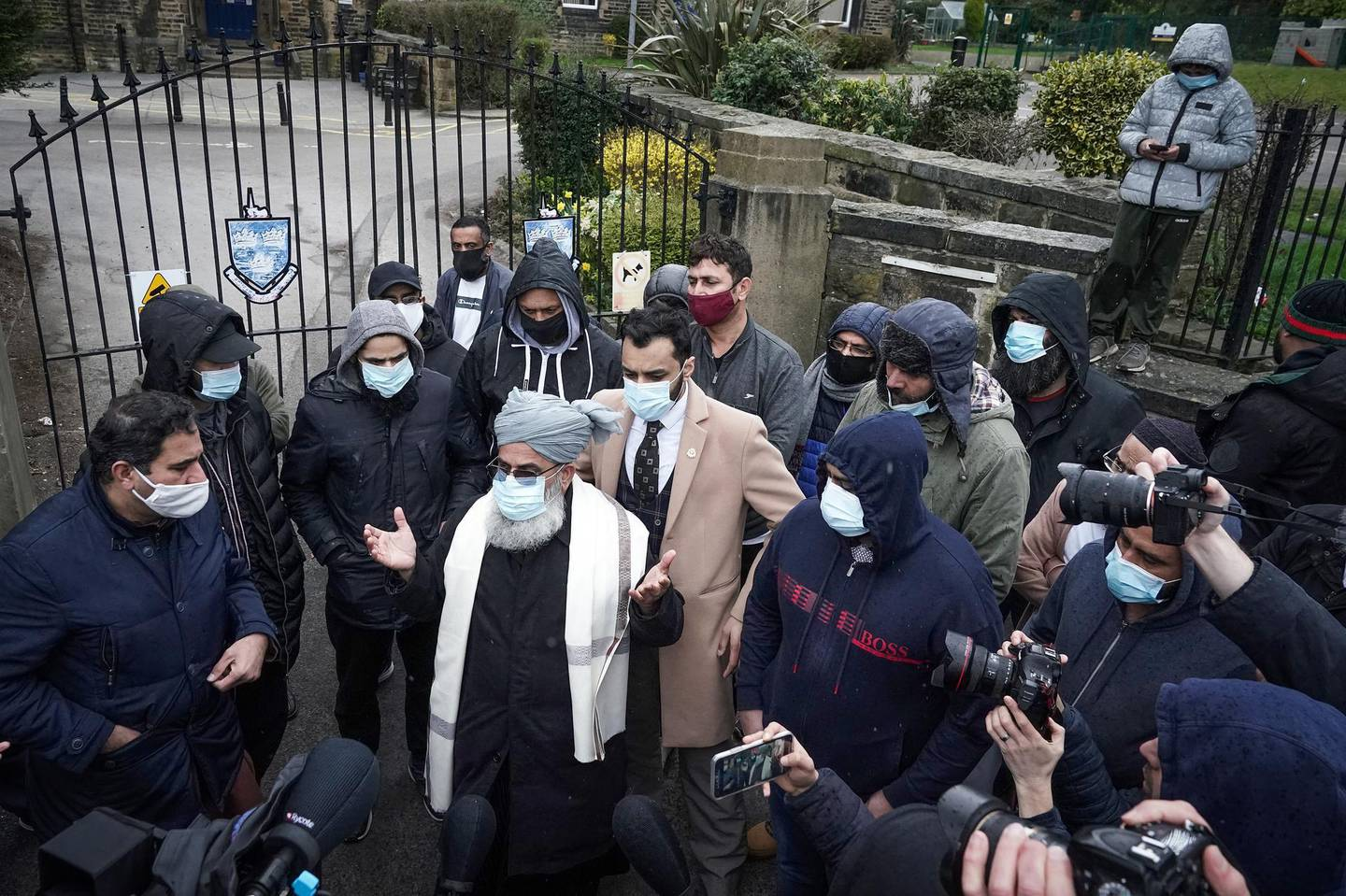 BATLEY, ENGLAND - MARCH 26: People gather outside the gates of Batley Grammar School, after a teacher was suspended for showing an image of the Prophet Muhammad in class, on March 26, 2021 in Batley, England. A few dozen people, including parents of students, gathered outside the school gates yesterday morning to protest the teacher's actions. The school issued an apology yesterday and said the teacher had been suspended. (Photo by Christopher Furlong/Getty Images)
