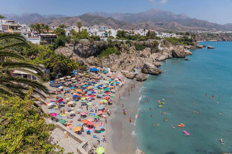 Nerja, Costa del Sol, Malaga Province, Andalusia, southern Spain, View from the Balcon de Europa, or Balcony of Europe, to the Playa Calahonda, Calahonda beach), It is the height of the season and the beach is packed with holiday makers. (Photo by: Education Images/Universal Images Group via Getty Images)