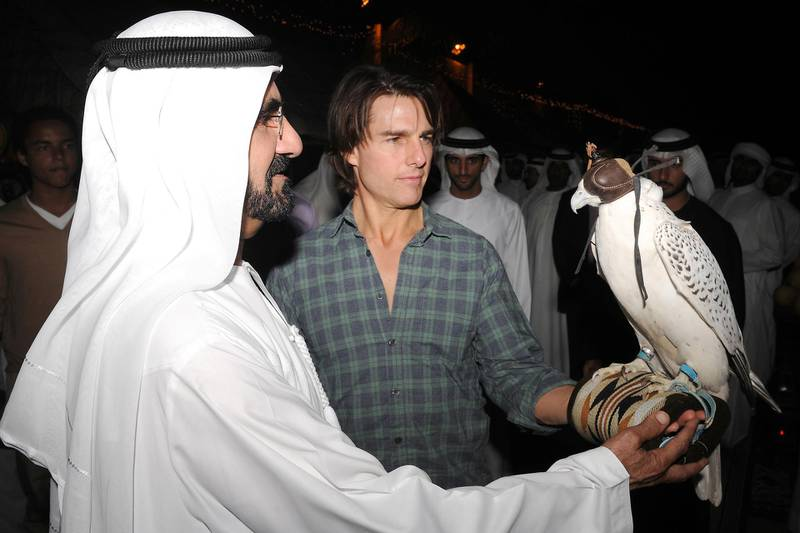 """A handout picture released by the government of Dubai shows Dubai ruler Sheikh Mohammed bin Rashed al-Maktoum explaining to Hollywood actor Tom Cruise (R) how to balance a falcon on his arm on November 2, 2010. Cruise is in Dubai shooting """"Mission: Impossible - Ghost Protocol"""". AFP PHOTO/HO == RESTRICTED TO EDITORIAL USE == (Photo by - / GOVERNMENT OFFICE / AFP)"""