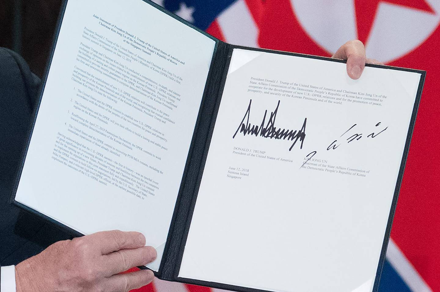 US President Donald Trump holds up a document signed by him and North Korea's leader Kim Jong Un following a signing ceremony during their historic US-North Korea summit, at the Capella Hotel on Sentosa island in Singapore on June 12, 2018.  Donald Trump and Kim Jong Un became on June 12 the first sitting US and North Korean leaders to meet, shake hands and negotiate to end a decades-old nuclear stand-off. / AFP / SAUL LOEB