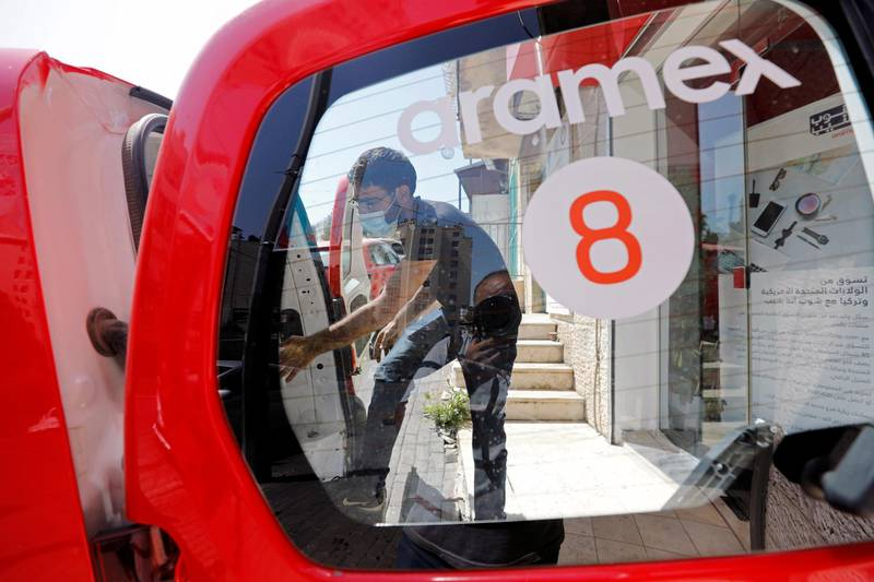 A delivery staff member wearing a protective mask unloads parcels from a vehicle outside Aramex office amid the coronavirus disease (COVID-19) crisis, in Bethlehem in the Israeli-occupied West Bank July 19, 2020. REUTERS/Mussa Qawasma