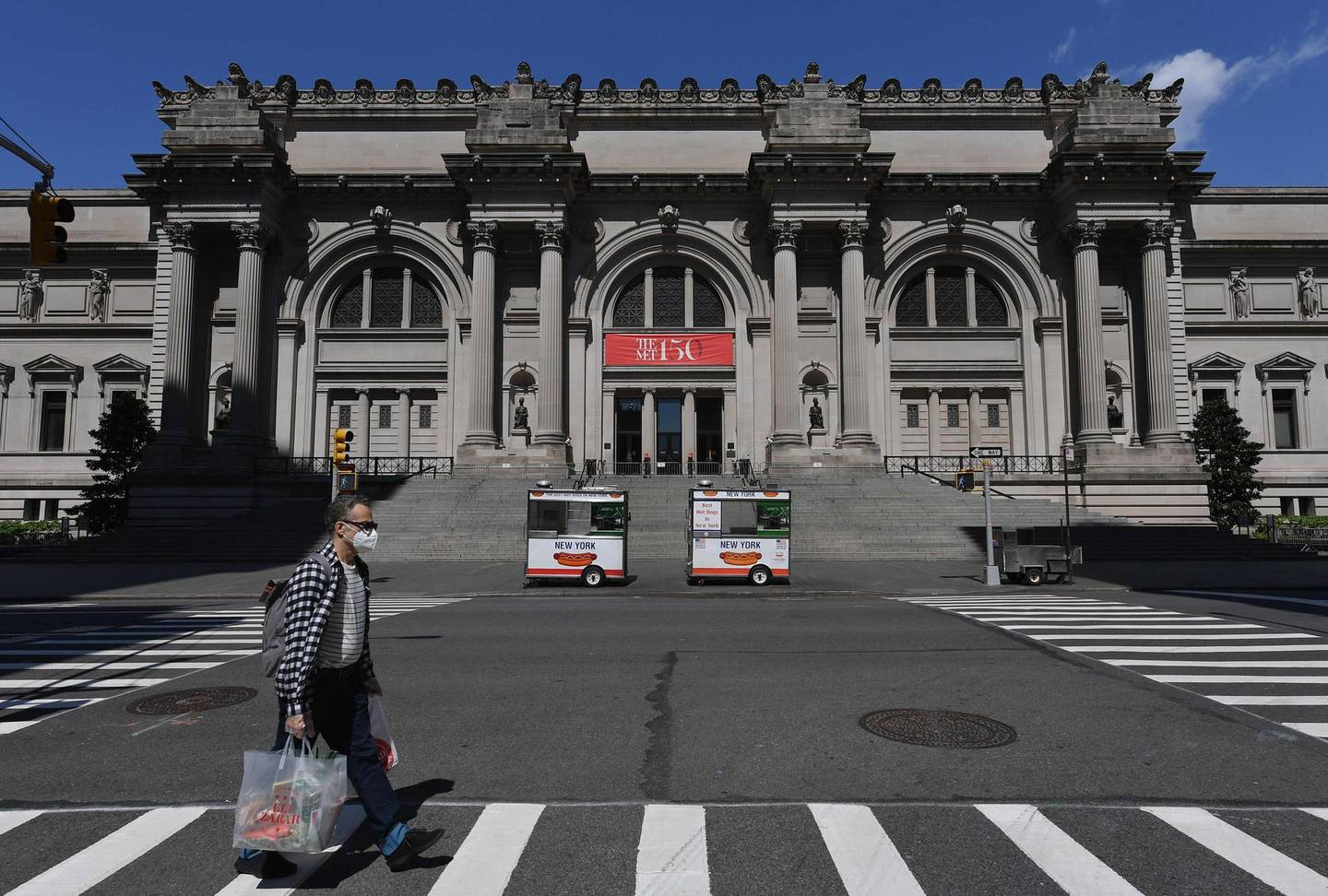 """(FILES) In this file photo taken on May 4, 2020 a man wearing a facemask walks past the Metropolitan Museum of Art """"The Met"""" in New York City.  New York's Metropolitan Museum plans to reopen in mid-August, """"or maybe a few weeks later,"""" with reduced hours and no tours to maintain social distancing, the museum said on May 19, 2020. / AFP / Angela Weiss"""