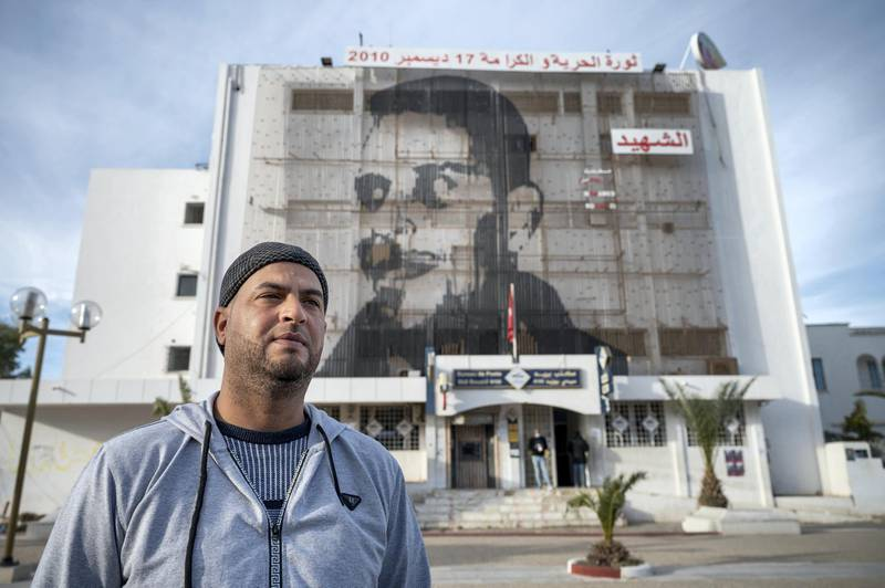 Kais Bouazizi stands beneath a giant mural to Mohamed Bouazizi in Sidi Bouzid, almost ten years to the day since the events that led to the revolution.