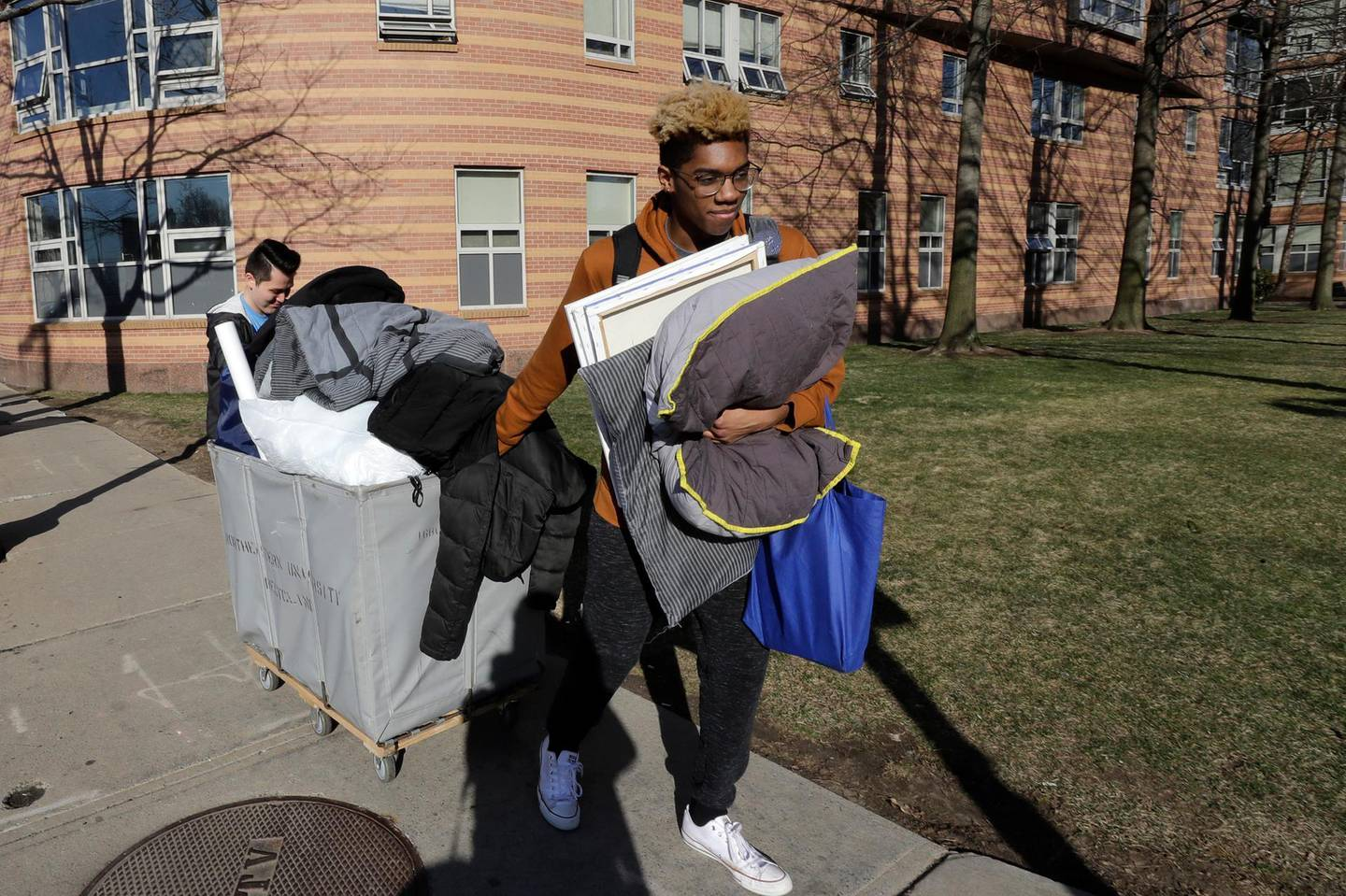 Northeastern University sophomore Philip Thomas, of Hamden, Conn., front, pulls a cart of belongings as he moves out of his residence hall as classmate Jarrett Anderson, of Las Vegas, left, assists him, Sunday, March 15, 2020, in Boston. Students have been asked by the school to move out of residence halls out of concern about the spread of the coronavirus. For most people, the new coronavirus causes only mild or moderate symptoms, such as fever and cough. For some, especially older adults and people with existing health problems, it can cause more severe illness, including pneumonia. The vast majority of people recover from the new virus. (AP Photo/Steven Senne)