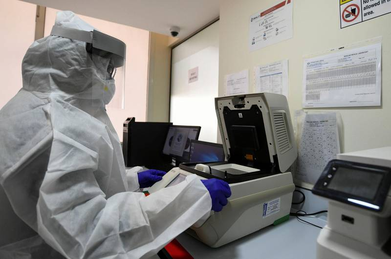 Abu Dhabi, United Arab Emirates - Lab technician wearing a protective suit and face shield carries out PCR testing at MenaLabs Medical Laboratory in Abu Dhabi. Khushnum Bhandari for The National