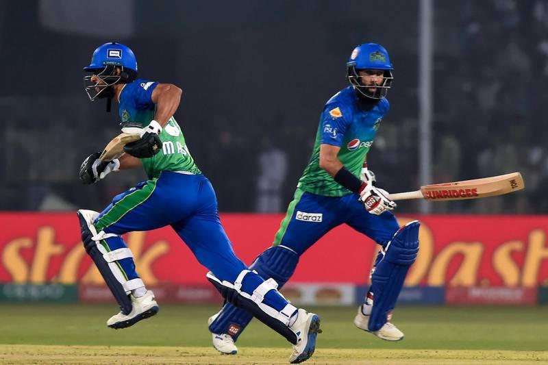 Multan Sultans's Moeen Ali (R) and Shan Masood run between the wicket during the Pakistan Super League (PSL) Twenty20 cricket match between Multan Sultans and Peshawar Zalmi at the Multan Cricket Stadium in Multan on February 26, 2020. (Photo by Arif ALI / AFP)