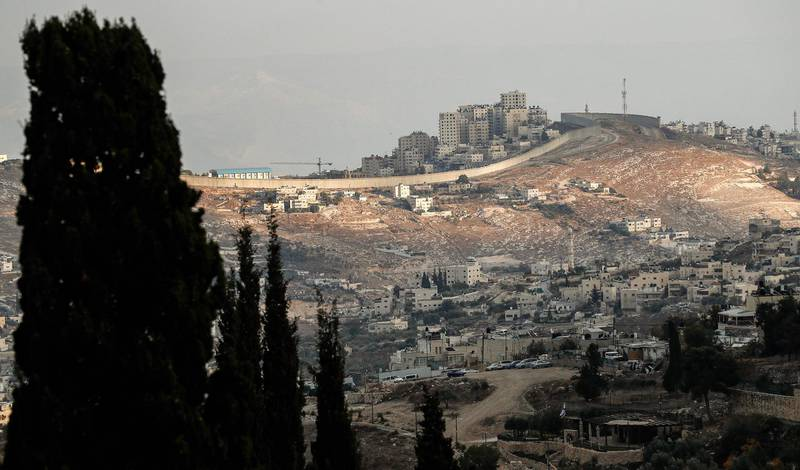 This picture taken on December 5, 2019 shows a section of Israel's controversial separation barrier from a hill top in Jerusalem.  / AFP / EMMANUEL DUNAND