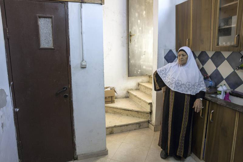 Fahima Shamasneh in the kitchen of her  tiny two room basement home in the East Jerusalem neighborhood of Sheik Jarrah on August 11,2017.  When the Shamasne family first moved into their home  in the 1960s, East Jerusalem was controlled by Jordan and their monthly rent was paid to  Jordanian authorities but since  Israel annexed East Jerusalem in 1967, the Shamasne family has paid their rent to Israel's general custodian in order to remain in the building. The family claims that their payments were suddenly rejected in 2009 , and they were informed that the property had been claimed by Israeli Jews whose ancestors had lived there decades previously.Although the family has spent years fighting to remain in the home , the Israeli high court has ruled that the family must evacuate the home before August 9. (Photo by Heidi Levine for The National).