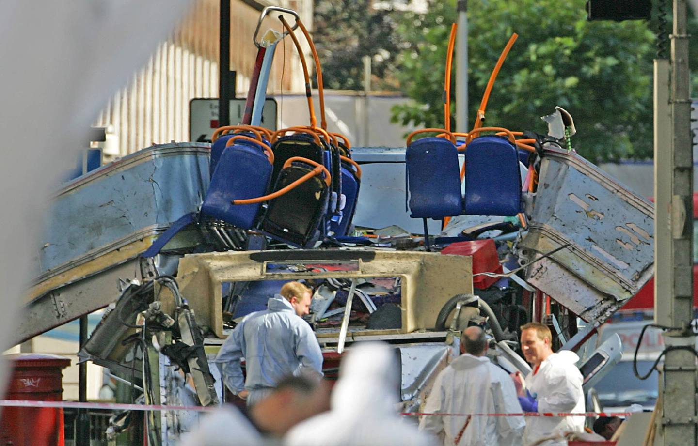 Forensic investigators collect evidences around the bombed out double-decker bus in Tavistock square in London 10 July 2005. At least 50 people were killed and 700 injured in the 07 July 2005 morning rush hour blasts on three underground trains and the bus. AFP PHOTO/ODD ANDERSEN (Photo by ODD ANDERSEN / AFP)