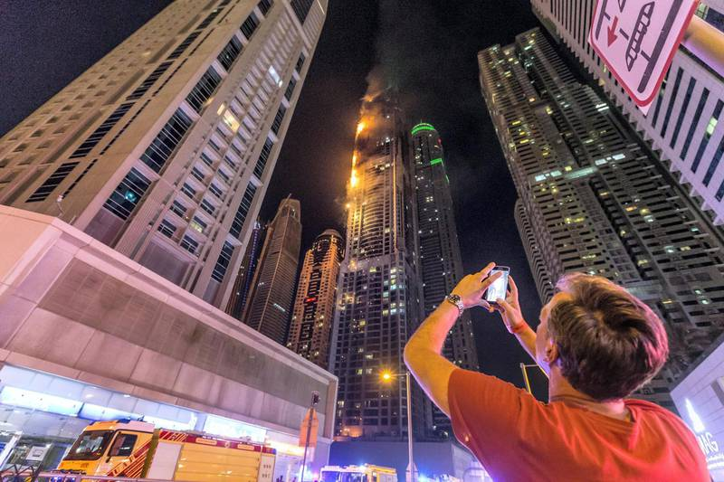 DUBAI. UNITED ARAB EMIRATES, 04 AUGUST 2017. A massive fire rips through The Marina Torch tower's southern corner. One of the many onlookers take a mobile phone picture. (Photo: Antonie Robertson) Journalist: None. Section: National.
