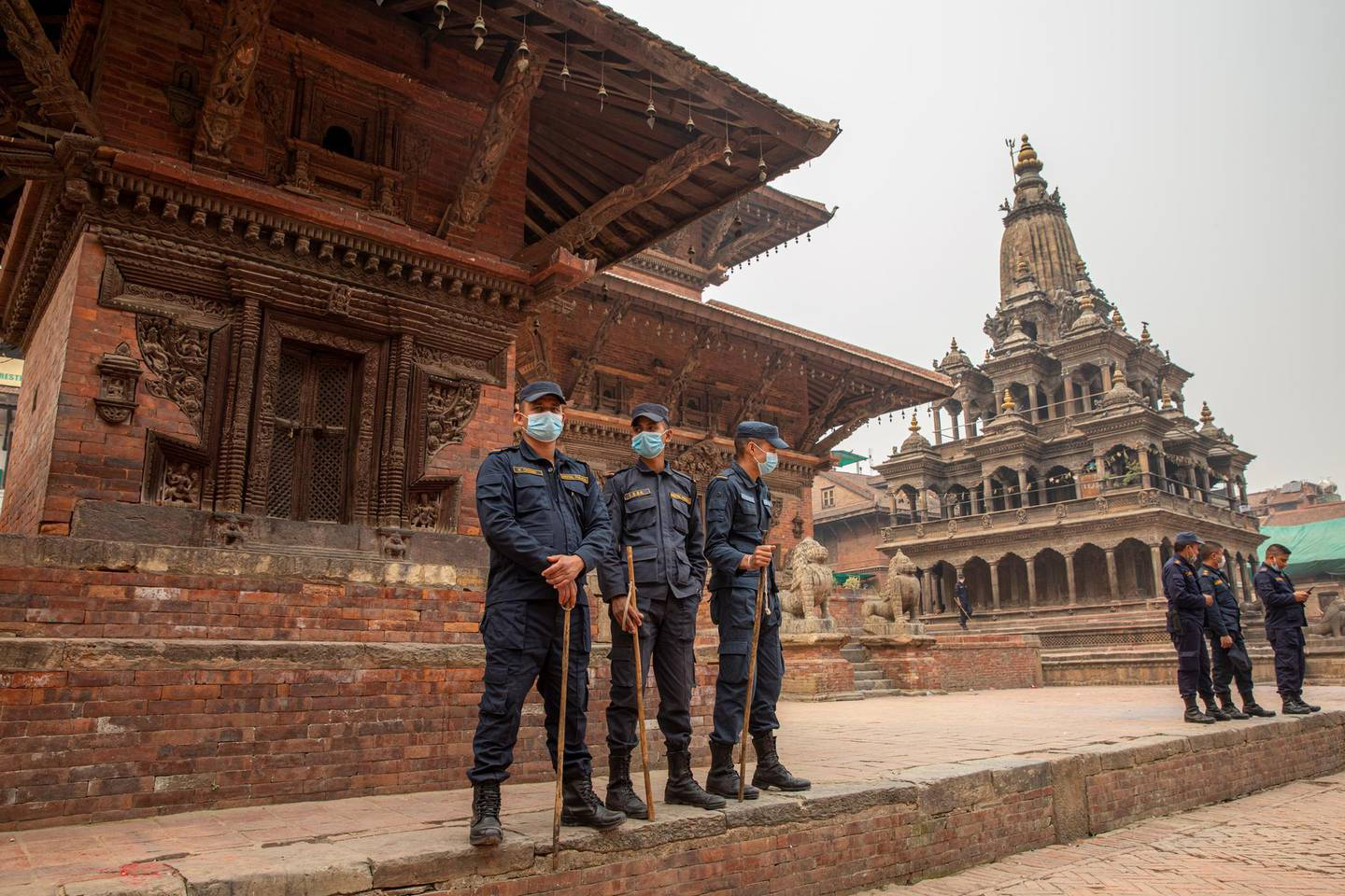 epa09102842 Nepalese police stands guard at Patan Durbar Square during celebrations of Holi Festival amidst Coronavirus restrictions in Kathmandu, Nepal, 28 March 2021. Holi, also known as the Festival of Colors, marks the beginning of spring and is celebrated all over Nepal and neighboring India. Nepal government restricted to celebrate the Holi festival by gathering crowd and organizing party due to the spread of the coronavirus COVID-19 disease.  EPA/NARENDRA SHRESTHA