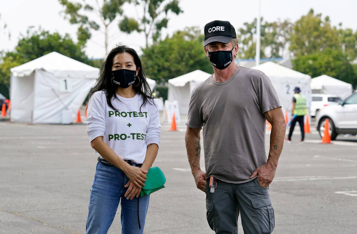 Ann Lee, left, CEO of Community Organized Relief Effort (CORE), and founder Sean Penn pose together at a CORE coronavirus testing site at Crenshaw Christian Center, Friday, Aug. 21, 2020, in Los Angeles. Penn says his organization CORE has made some strides against the coronavirus and he's keeping its mission going by expanding testing and other relief services. (AP Photo/Chris Pizzello)