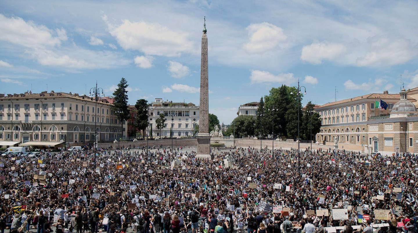 People gather calling for justice for George Floyd, who died May 25 after being restrained by police in Minneapolis, USA, in Rome's People's Square, Sunday, June 7, 2020. People have been protesting throughout Italy to denounce the police killing of George Floyd and show solidarity with anti-racism protests in the U.S. and elsewhere. (Roberto Monaldo/LaPresse via AP)