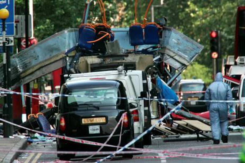 FILE -  In this July 7, 2005 file photo, a forensic officer walks next to the wreckage of a double decker bus with its top blown off and damaged cars scattered on the road at Tavistock Square in central London. European security officials said Wednesday Sept. 29, 2010, a terror plot to wage Mumbai-style shooting sprees or other low-budget attacks in Britain, France and Germany is still active and that sites in Pakistan _ where the threat was intercepted _ are being targeted for al-Qaida operatives. (AP Photo/Sang Tan, File)