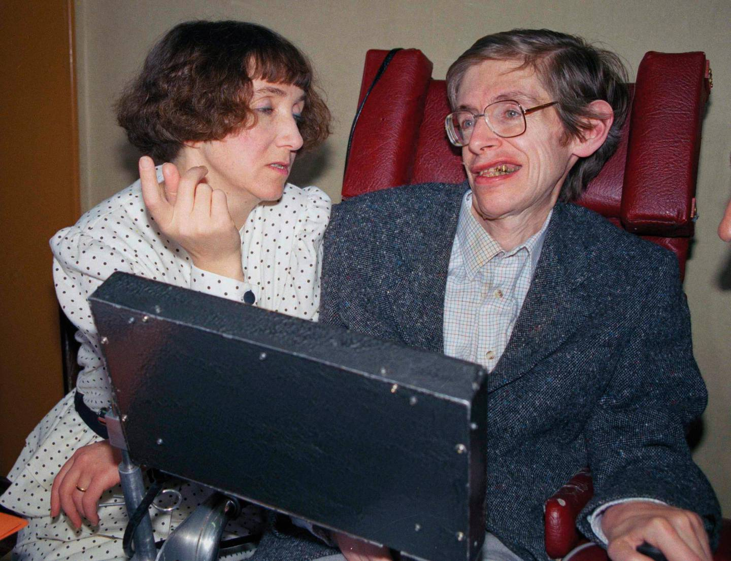British astrophysicist Dr. Stephen Hawking, 47, answers newsmen with the help of his computer and the assistance of his wife Jane, in Paris, March 3, 1989.  Hawking, who has a motor neuron disease communicates with the help of a voice-equipped computer.  (AP Photo/Lionel Cironneau)