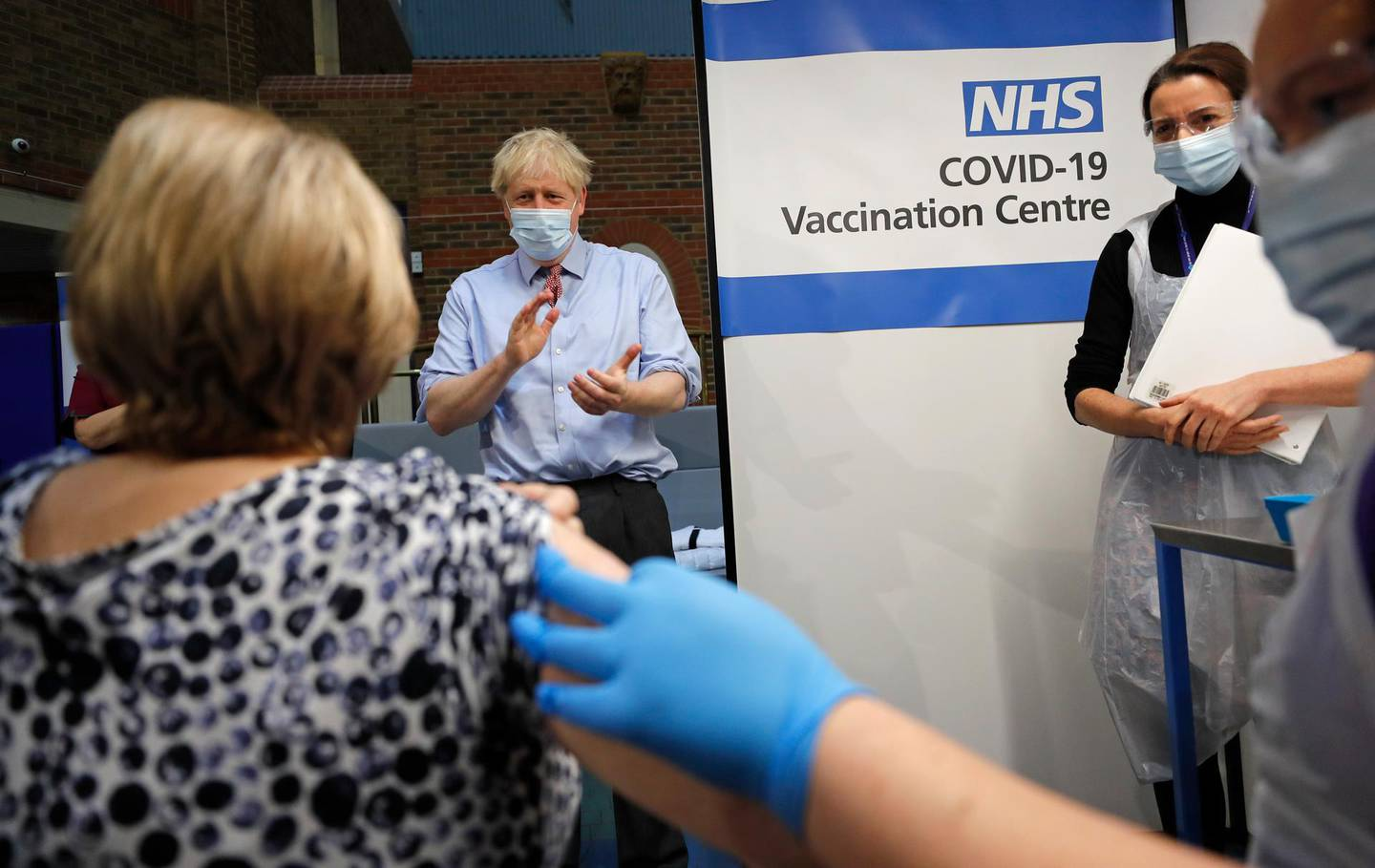 British Prime Minister Boris Johnson applauds after nurse Rebecca Cathersides administered the Pfizer-BioNTech COVID-19 vaccine to Lyn Wheeler at Guy's Hospital in London, Tuesday, Dec. 8, 2020. U.K. health authorities rolled out the first doses of a widely tested and independently reviewed COVID-19 vaccine Tuesday, starting a global immunization program that is expected to gain momentum as more serums win approval. (AP Photo/Frank Augstein, Pool)
