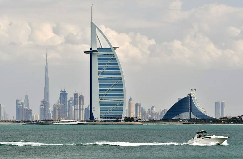 A picture taken on January 8, 2018 shows the skyline of Dubai with the Burj al-Arab in the foreground and Burj Khalifa (L) in the background. (Photo by GIUSEPPE CACACE / AFP)