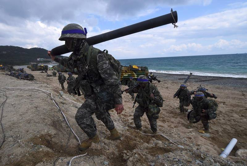 """(FILES) This file photo taken on April 2, 2017 shows South Korean Marines moving into position on a beach during a joint landing operation by US and South Korean Marines in the southeastern port of Pohang. The US military has indefinitely postponed major joint exercises with South Korea, an official told AFP on June 14, 2018, acting on President Donald Trump's pledge to halt the """"provocative"""" military drills following his summit with North Korea's Kim Jong Un. / AFP / JUNG Yeon-Je"""