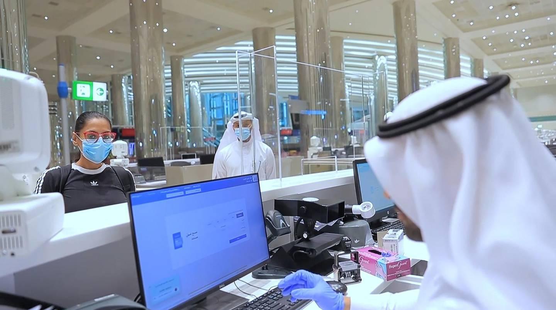 An immigration official checks documents of passenger at Dubai Airport. WAM