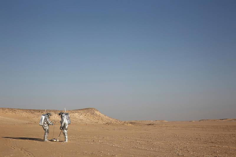 Two scientists test space suits and a geo-radar for use in a future Mars mission in the Dhofar desert of southern Oman on Wednesday, Feb. 7, 2018. The desolate desert resembles Mars so much that more than 200 scientists from 25 nations organized by the Austrian Space Forum are using it for the next four weeks to field-test equipment. (AP Photo/Sam McNeil)