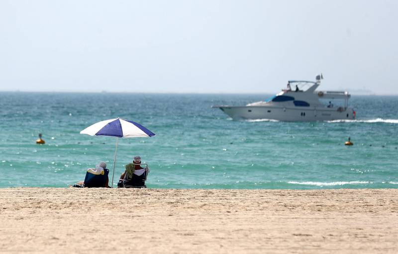 Dubai, United Arab Emirates - Reporter: N/A. News/Weather. A couple watch a yacht go passed from the beach on a hot day in Dubai. Sunday, June 14th, 2020. Dubai. Chris Whiteoak / The National