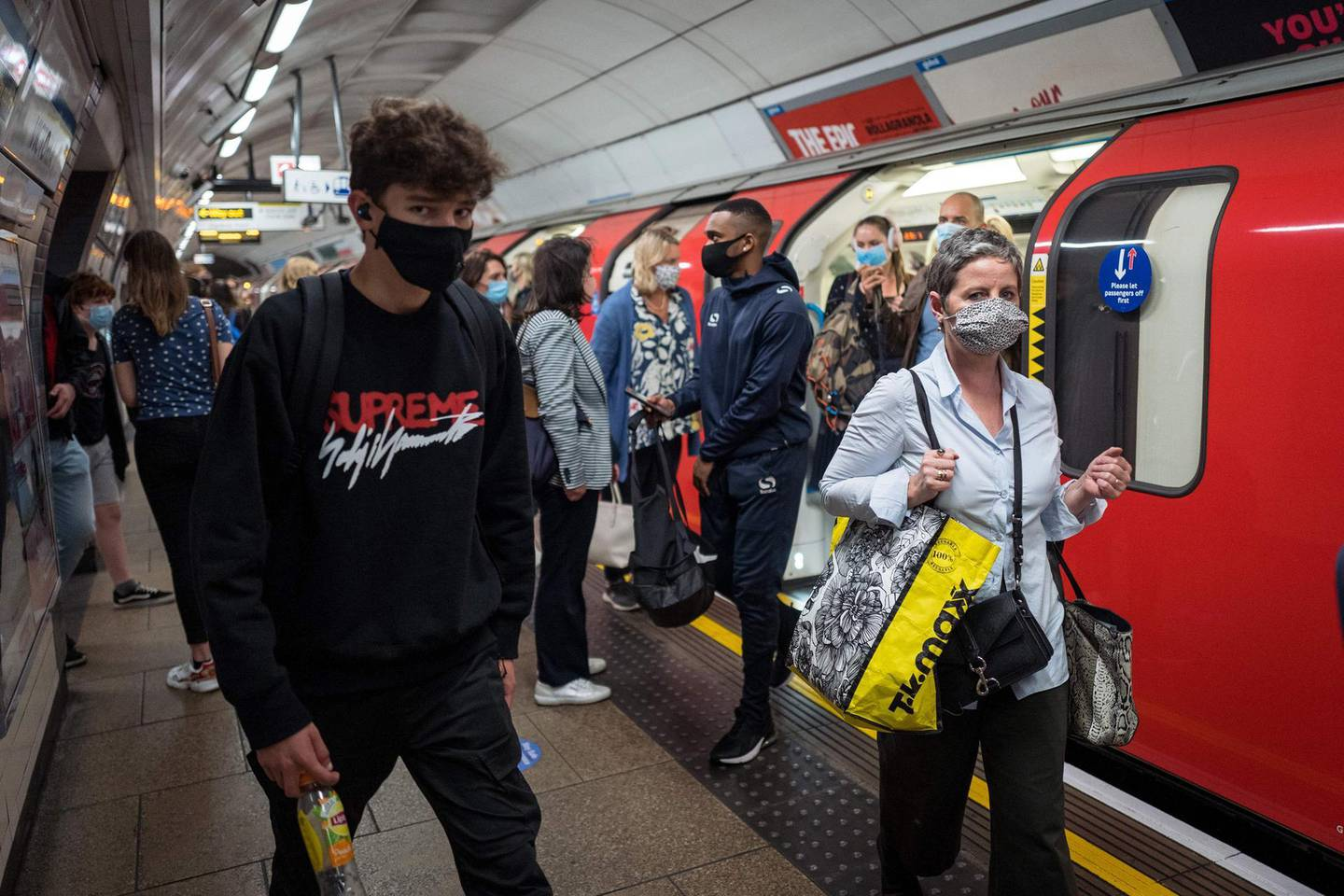 Commuters wearing a face mask or covering due to the COVID-19 pandemic, walk past a London underground tube train at Victoria station, during the evening 'rus hour' in central London on September 23, 2020..  The UK on Wednesday reported 6,178 new coronavirus cases, a marked jump in the daily infection rate that comes a day after Prime Minister Boris Johnson unveiled new nationwide restrictions. / AFP / Tolga AKMEN