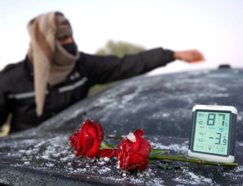 Rukna Region, Al Ain, United Arab Emirates, January 11, 2021. Fahad Mohammed of the UAE Storm Centre scrapes off some ice build up on a car during low temperatures at Rukna region, Al Ain which went down to -4 degrees Celsius  at one point.                     Victor Besa/The NationalSection:  NAReporter:  Haneen Dajani