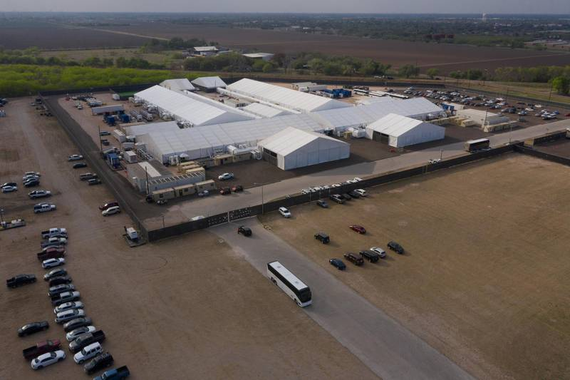 A tour bus exits a U.S. Customs and Border Protection temporary processing center after dropping off migrants in Donna, Texas, U.S., March 15, 2021. Picture taken with a drone. REUTERS/Adrees Latif