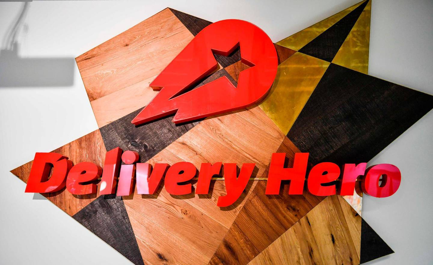 (FILES) This file photo taken on June 27, 2017 shows a logo in a lounge area of the global headquarters of online food ordering and delivery giant Delivery Hero in Berlin. German takeaway giant Delivery Hero on December 13, 2019 said it had agreed to buy South Korea's largest food delivery app Woowa in a 3.6 billion euro ($4 billion) deal aimed at beefing up its presence in Asia. / AFP / John MACDOUGALL