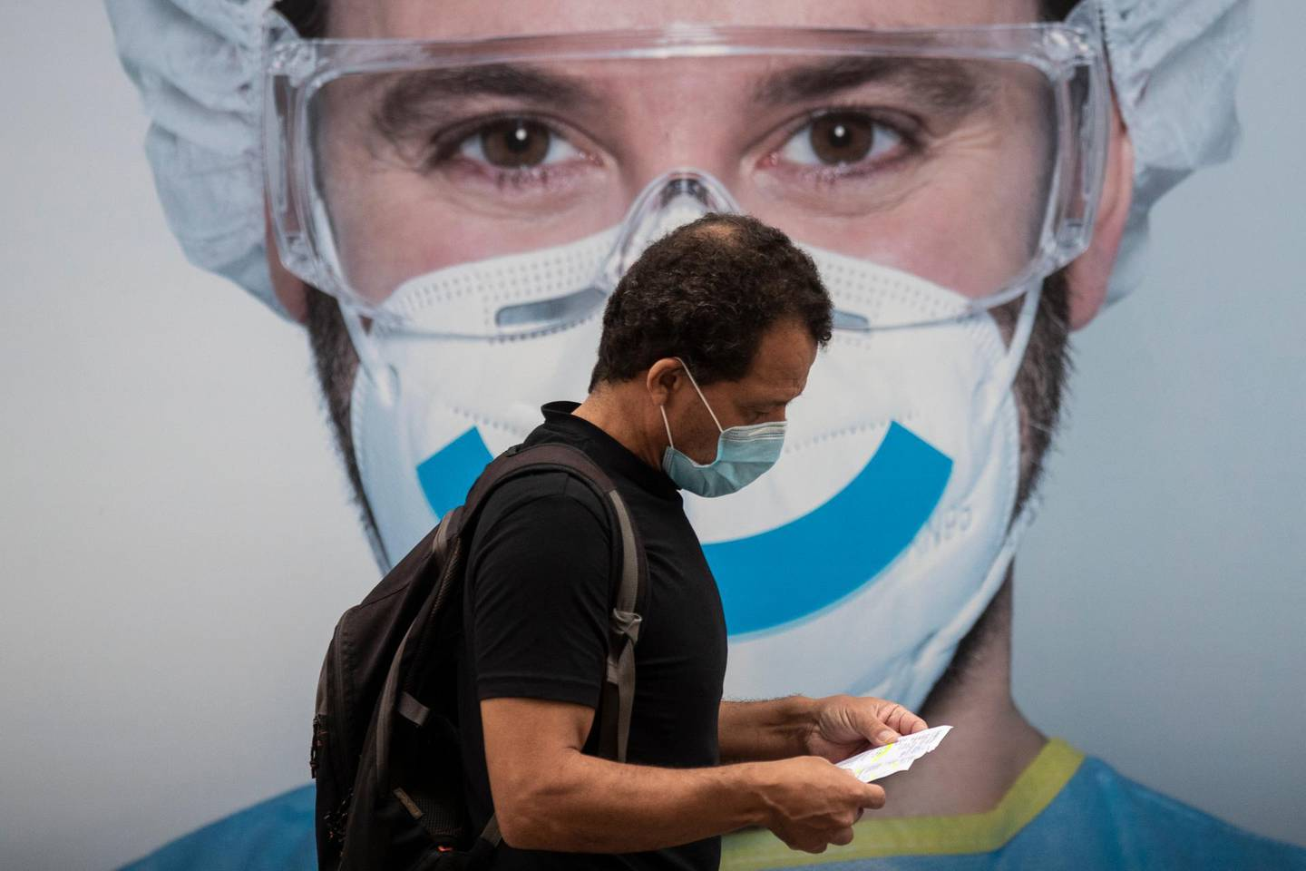 A man wearing a face mask to prevent the spread of coronavirus walks in the Vallecas neighborhood in Madrid, Spain, Saturday, Sept. 19, 2020. Authorities in Madrid, the European capital experiencing the worst second-wave outbreak, are introducing new curbs on social gatherings starting Monday. (AP Photo/Manu Fernandez)