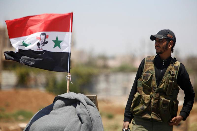 FILE PHOTO: A Syrian army soldier stands next to a Syrian flag in Umm al-Mayazen, in the countryside of Deraa, Syria, July 10, 2018. REUTERS/Omar Sanadiki/File Photo