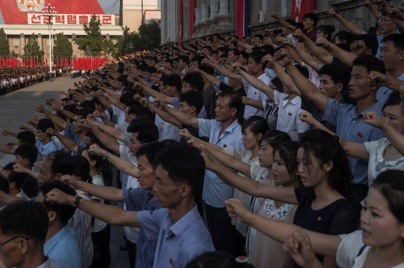 """People wave banners and shout slogans as they attend a rally in support of North Korea's stance against the US, on Kim Il-Sung square in Pyongyang on August 9, 2017.  US President Donald Trump said the United States' nuclear arsenal was """"more powerful than ever"""" in a fresh warning to North Korea over its repeated missile tests. / AFP PHOTO / KIM Won-Jin"""