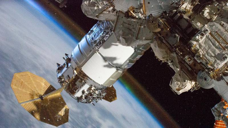 """This NASA photo obtained April 5, 2021 shows the Cygnus resupply ship, with its prominent cymbal-shaped UltraFlex solar arrays, from Northrop Grumman  pictured on March 28, 2021 attached to the International Space Station's Unity module. - Earth's atmospheric glow is seen blanketing the horizon as the orbital complex flew 262 miles above Ethiopia on the African continent. (Photo by Handout / NASA / AFP) / RESTRICTED TO EDITORIAL USE - MANDATORY CREDIT """"AFP PHOTO /NASA/HANDOUT"""" - NO MARKETING - NO ADVERTISING CAMPAIGNS - DISTRIBUTED AS A SERVICE TO CLIENTS"""