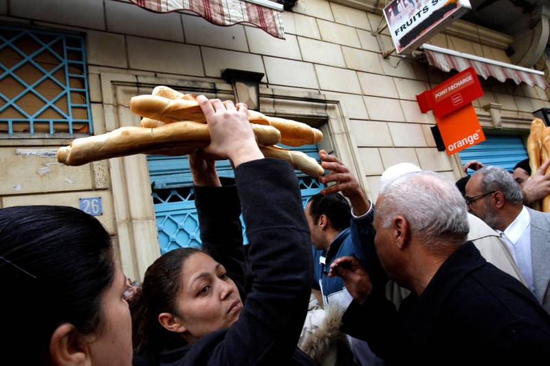 FILE - In this Jan. 17, 2011 file photo, a woman leaves a bakery after buying bread in the center of Tunis. Some call it dangerous, others embrace it as revolutionary: an initiative by Tunisia's president to make inheritance and marriage rules fairer to women has divided his country and reverberated across the Muslim world.  (AP Photo/Christophe Ena, File)