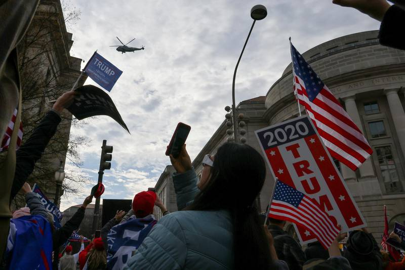 Marine One, carrying U.S. President Donald Trump, passes over people attending a rally to protest the results of the election in front of Supreme Court building, in Washington, U.S., December 12, 2020. REUTERS/Jonathan Ernst