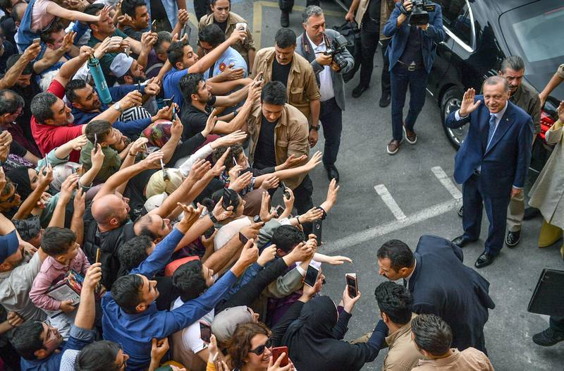 TOPSHOT - Turkey's President Recep Tayyip Erdogan, leader of the Justice and Development Party (AKP) is greeted by supporters as he and his wife leave the polling station after casting their votes during snap twin Turkish presidential and parliamentary elections in Istanbul on June 24, 2018. Erdogan has won tightly-contested presidential polls, the election authority said on June 25, extending his 15-year grip on power as the opposition complained bitterly about the conduct of the vote count. / AFP / BULENT KILIC