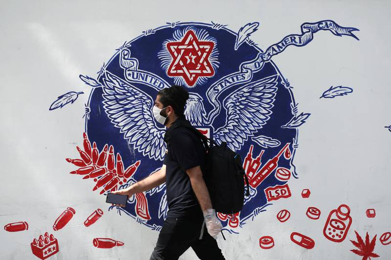 An Iranian man wearing a protective mask walks past a wall of a former U.S Embassy, following the outbreak of the coronavirus disease (COVID-19), in Tehran, Iran, June 28, 2020. WANA (West Asia News Agency) via REUTERS ATTENTION EDITORS - THIS PICTURE WAS PROVIDED BY A THIRD PARTY