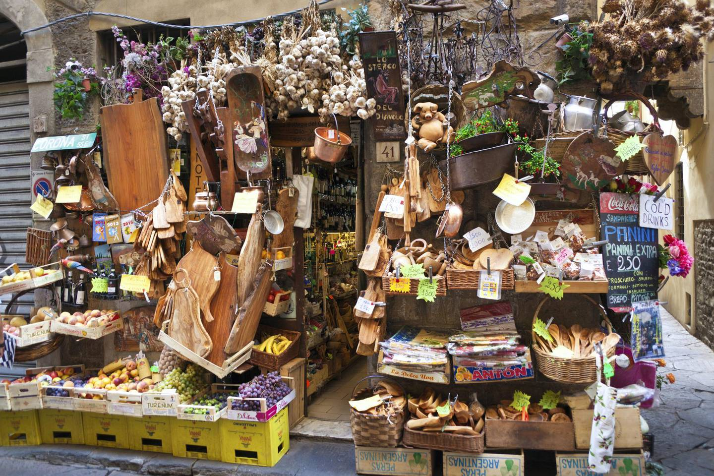 Florence, Italy - Sep 22, 2015: Urban street scene of an elaborate, crowded, charming front entrance display at a retail grocery store, featuring fruits, vegetables, and housewares, Florence, Italy.