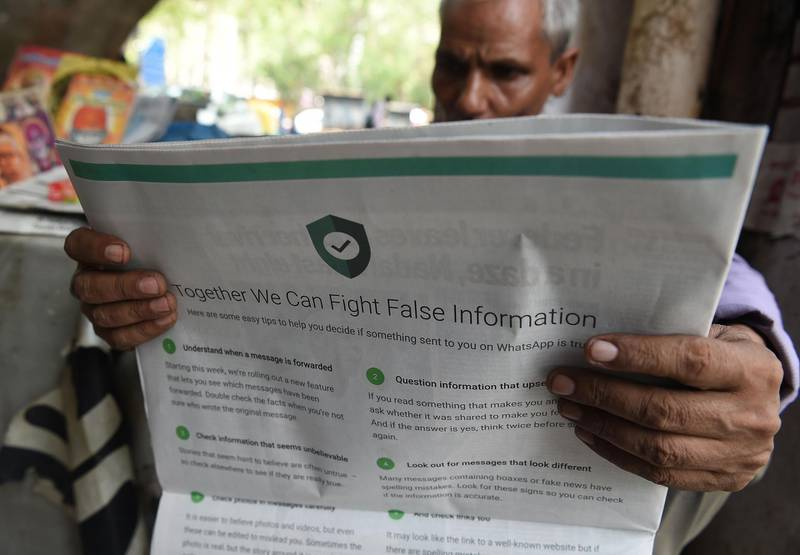 This photo illustration shows an Indian newspaper vendor reading a newspaper with a full back page advertisement from WhatsApp intended to counter fake information, in New Delhi on July 10, 2018.  Facebook owned messaging service WhatsApp on July 10 published full-page advertisements in Indian dailies in a bid to counter fake information that has sparked mob lynching attacks across the country.  / AFP / Prakash SINGH