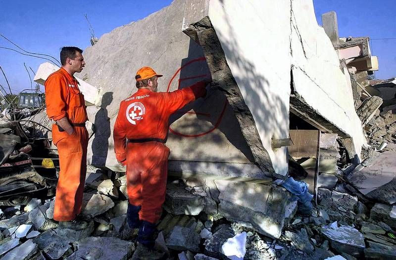Members of a Swiss rescue team make markings on a wall of building in the town of Bhuj, 29 January 2001, that was destroyed in the massive 7.9 magnitude earthquake that struck northwestern India 26 January. The Swiss team is part of a larger international contingent helping out local relief work. An estimated 20,000 people are thought to have been killed in the quake, the worst to hit India for 50 years.     AFP PHOTO/Arko DATTA (Photo by ARKO DATTA / AFP)