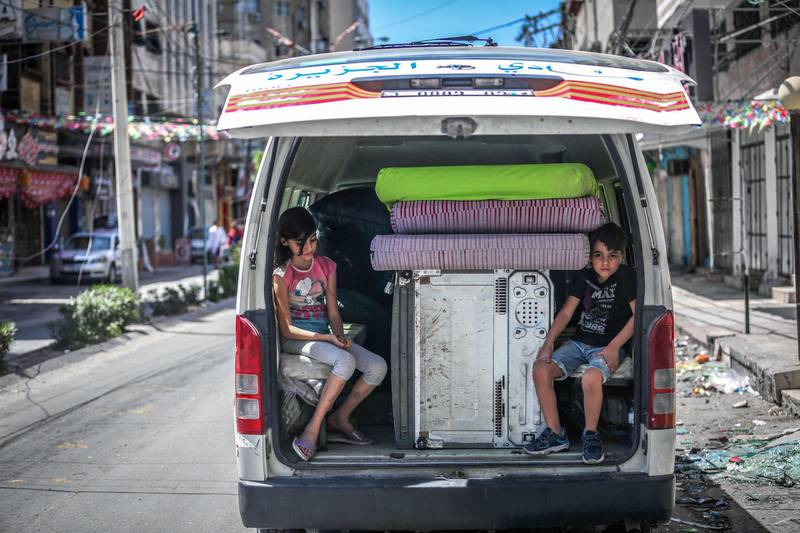 TOPSHOT - Palestinian children sit in the back of a van loaded with salvaged belongings from their home at the Al-Jawhara Tower in Gaza City, on May 17, 2021, which was heavily damaged by  Israeli airstrikes. / AFP / ANAS BABA