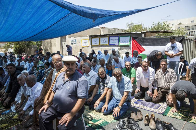 Men gather for a protest support prayer on the road outside the Shamasneh home for Friday noon prayer   in the East Jerusalem neighborhood of Sheik Jarrah on August 11,2017.  When the Shamasne family first moved into their home  in the 1960s, East Jerusalem was controlled by Jordan and their monthly rent was paid to  Jordanian authorities but since  Israel annexed East Jerusalem in 1967, the Shamasne family has paid their rent to Israel's general custodian in order to remain in the building. The family claims that their payments were suddenly rejected in 2009 , and they were informed that the property had been claimed by Israeli Jews whose ancestors had lived there decades previously.Although the family has spent years fighting to remain in the home , the Israeli high court has ruled that the family must evacuate the home before August 9. (Photo by Heidi Levine for The National).