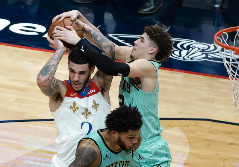 New Orleans Pelicans guard Lonzo Ball, left, and Charlotte Hornets guard LaMelo Ball reach for the ball during the second half of an NBA basketball game in New Orleans, Friday, Jan. 8, 2021. A jump ball was called. (AP Photo/Derick Hingle)
