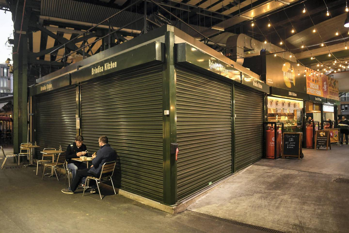 LONDON, ENGLAND - NOVEMBER 04: Two men are seen sat at a table outside a shut business in Borough Market on November 4, 2020 in London, England. Non-essential businesses, including pubs and restaurants, will be forced to close from Thursday, Nov 5, following a new national lockdown in England. (Photo by Peter Summers/Getty Images)
