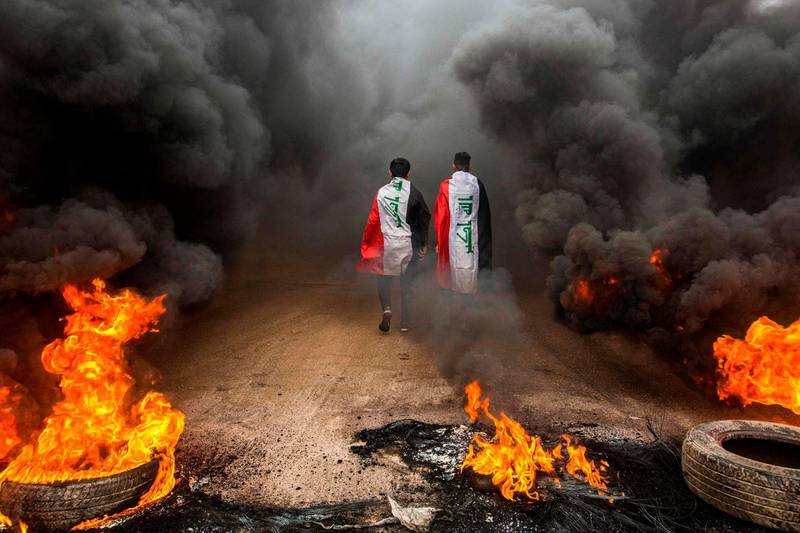 TOPSHOT - Anti-government protesters draped in Iraqi national flags walk into clouds of smoke from burning tires during a demonstration in the southern city of Basra on November 17, 2019, as protesters cut-off roads and activists call for a general strike. Iraqis flooded the streets of the capital and southern cities in a general strike that bolstered the weeks-long movement demanding a government overhaul. Protesters cut roads in the oil-rich port city of Basra by burning tyres and in Hillah, south of Baghdad, students and other activists massed in front of the provincial headquarters. / AFP / Hussein FALEH