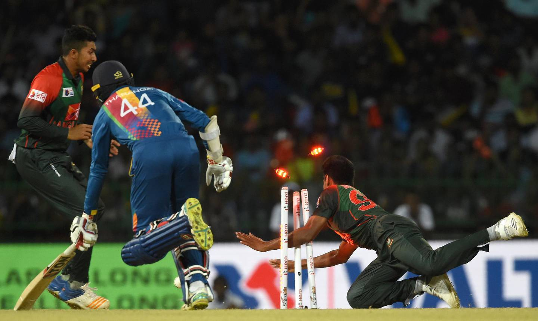 Bangladesh cricketer Mustafizur Rahman (R) dismisses Sri Lanka's Upul Tharanga (C) during the sixth Twenty20 (T20) international cricket match between Bangladesh and Sri Lanka of the tri-nation Nidahas Trophy at the R. Premadasa stadium in Colombo on March 16, 2018. / AFP PHOTO / ISHARA S. KODIKARA